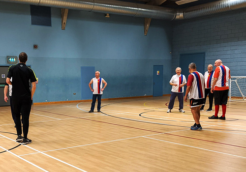 5 older men playing walking football, with their coach
