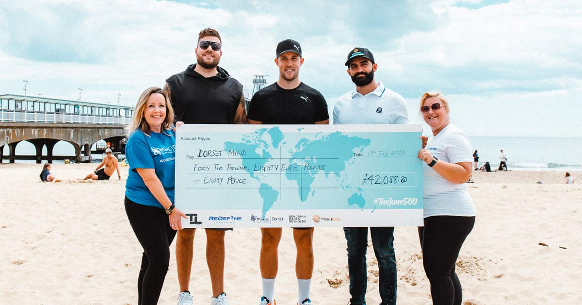 Five People Holding A Large Size Cheque On The Beachpresented For The June 500 Challenge