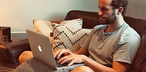 Man Sitting On Sofa Writing A Blog On His Laptop