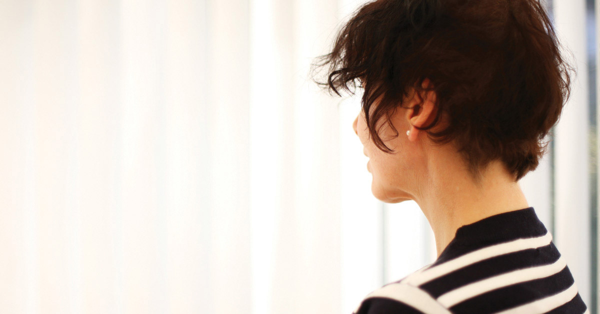 Woman In A Stripey Top Looking Away From The Camera