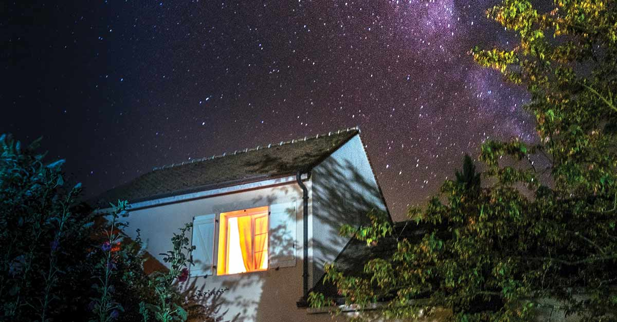 Image Shows A House With A Lit Window And The Sky Lit Up Behind It